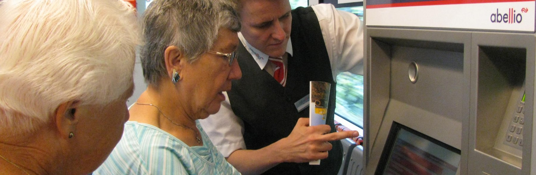 Abellio Germany employee helping elderly women with purchasing tickets
