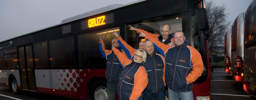 Five Qbuzz employees pointing at a Qbuzz bus