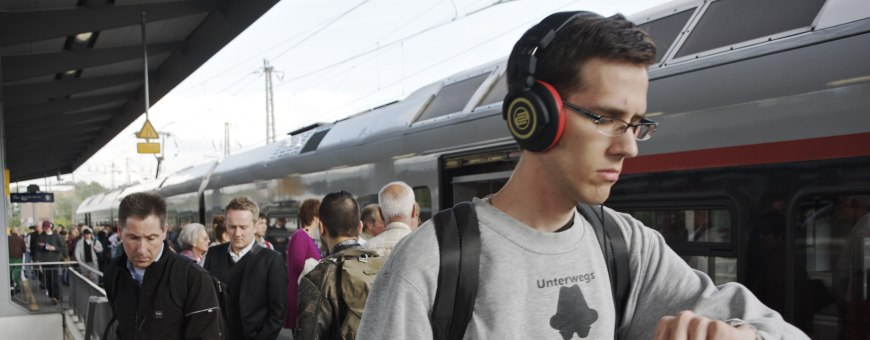 Young man wearing headphones on a platform looking at his watch