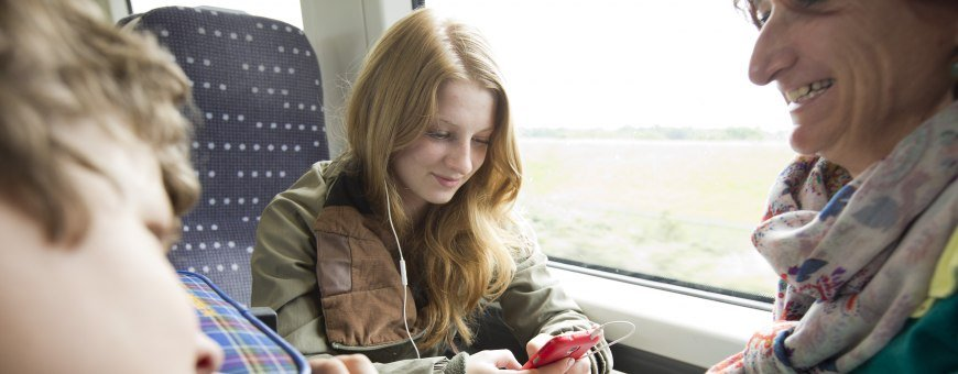 A teenage girl playing with her phone on an abellio greater anglia train