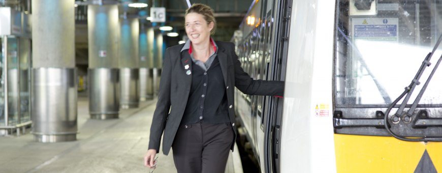 Female conductor waiting outside a train