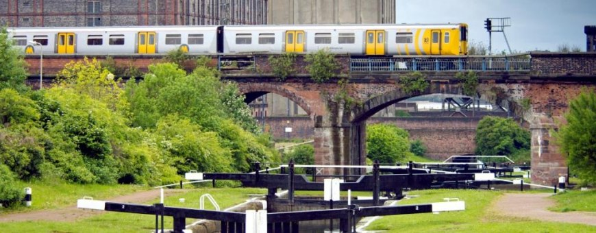 train crossing viaduct with canal lock gates in foreground
