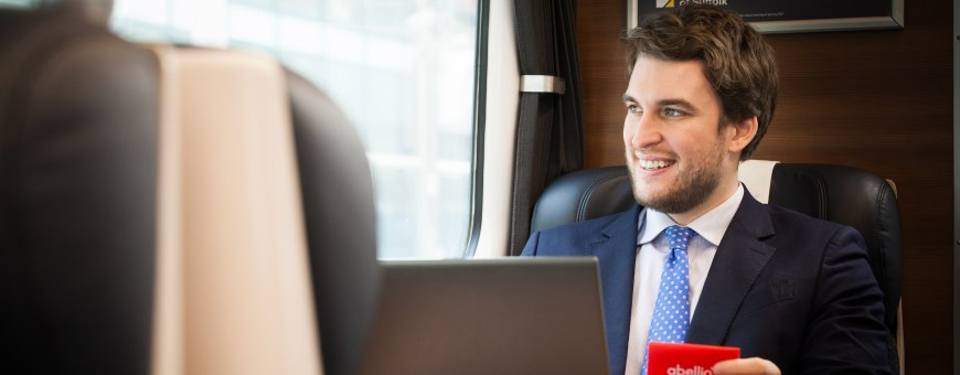 man on train looking out of window with abellio card holder in his hand
