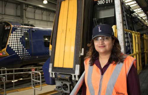 <p>Syeda Ghufran, ScotRail Engineering Director, standing in front of a ScotRail train</p>