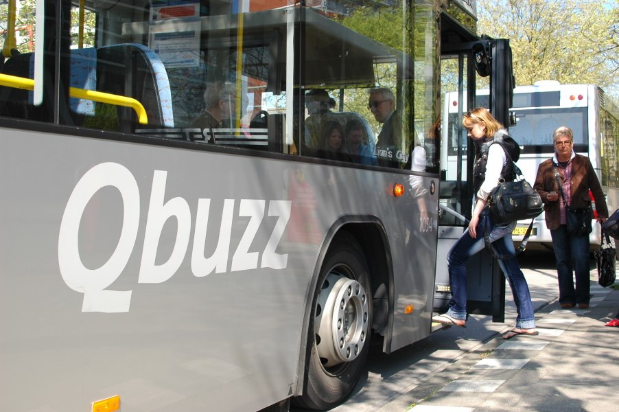 Young woman getting on a Qbuzz bus